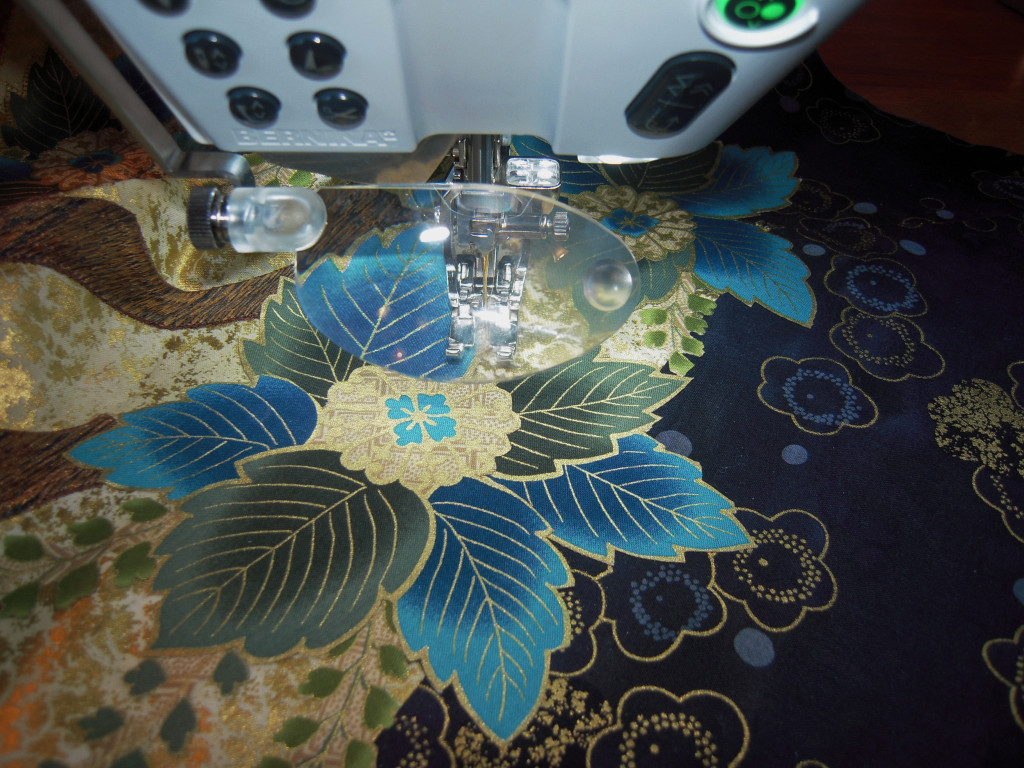 Stitching down a broiderie perse cutout from the Hoffman challenge fabric.